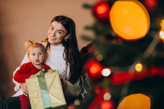 Мать с дочерью сидит у елки