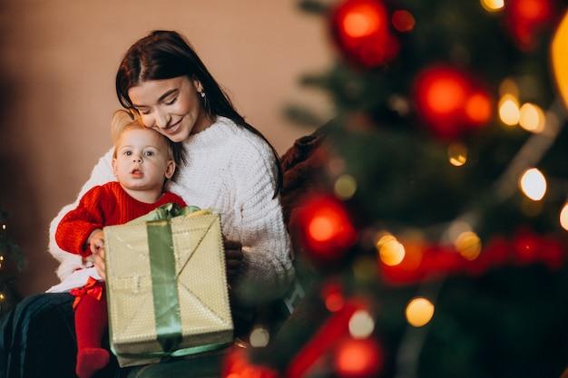 クリスマスツリーのそばに座っている娘を持つ母