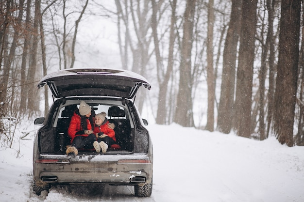 Mother with daughter sitting in car in winter