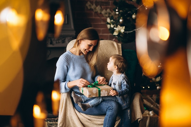 Mother with daughter sitting in chair by christmas tree