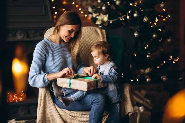 Madre con la figlia che si siede nella sedia dall'albero di natale