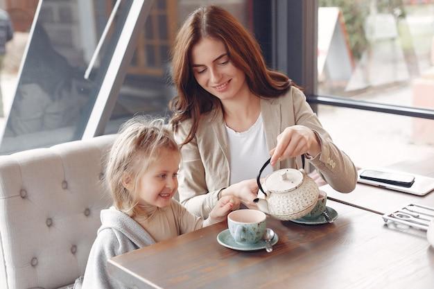カフェに座っている娘を持つ母