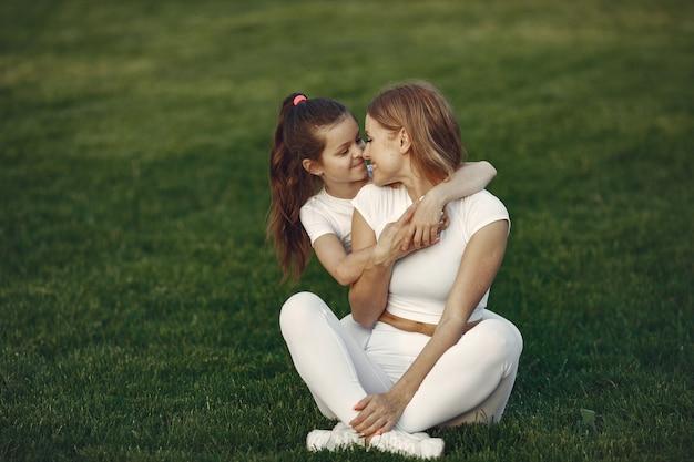 Мать с дочерью, сидя на траве