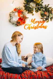 Mother with daughter sitting on sofa on christmas eve