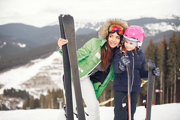 娘のスキーを持つ母。雪山の人々。
