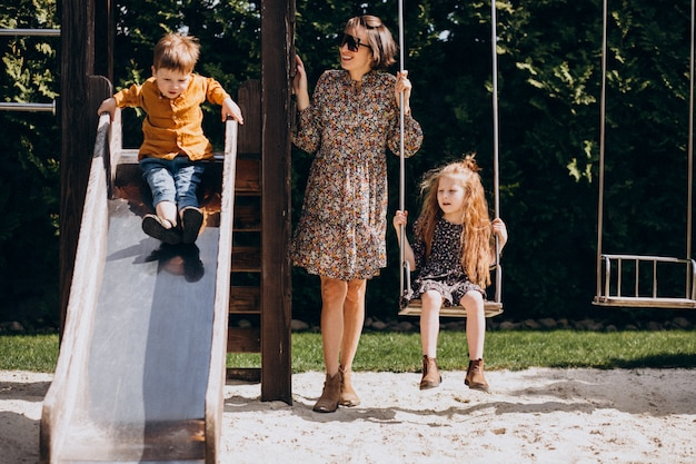 Mother with daughter and son swinging and sliding