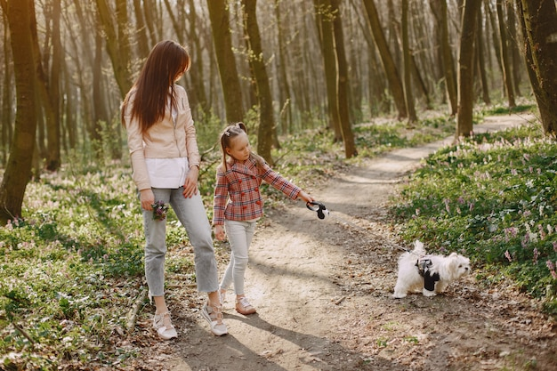 Mother with daughter in a spring forest with dog