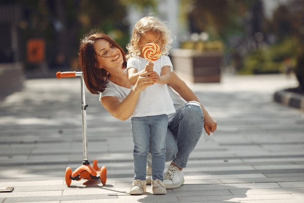 Madre con figlia in un parco di primavera con il pattino