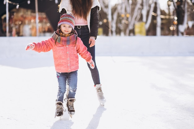 Mother with daughter teaching ice skating on a rink