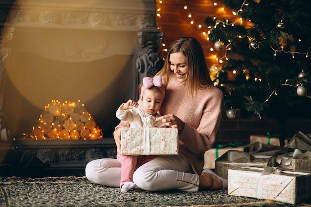 Madre con la figlia che disimballa i regali di natale dall'albero di natale