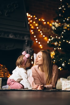 Mother with daughter unpacking christmas presents by christmas tree
