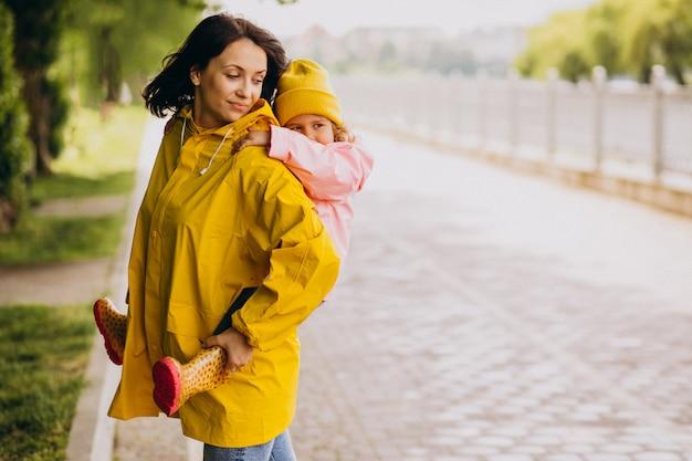 Мать с дочерью гуляет в парке под дождем в резиновых сапогах