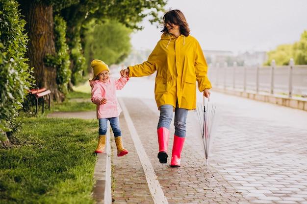 Madre con la figlia che cammina nel parco sotto la pioggia che indossa stivali di gomma