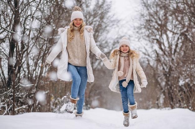Мать с дочерью гуляют вместе в зимнем парке