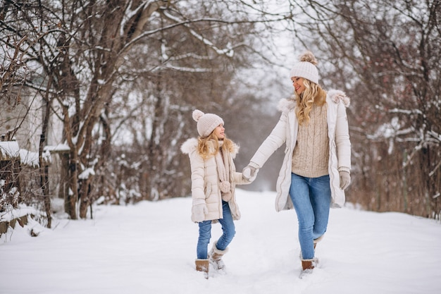 Mother with daughter walking together in a winter park