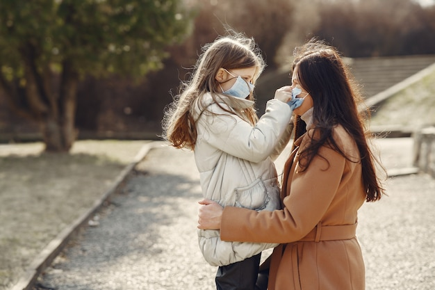 Mother with daughter walks outside in masks