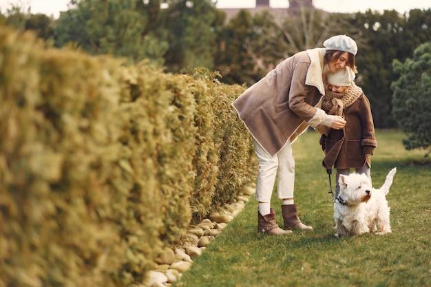 La madre con la figlia cammina con un cane