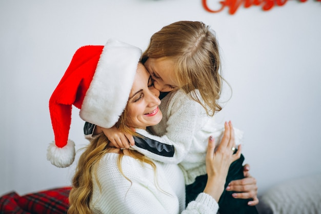 Mother with daughter wearing christmas hat