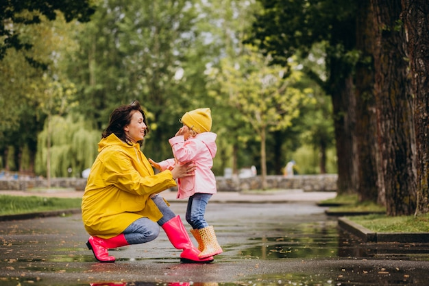 雨の天候の中を歩くレインコートと長靴を着ている娘を持つ母