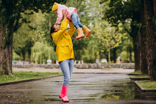 Mother with daughter wearing rain coat and rubber boots walking in a rainy weather