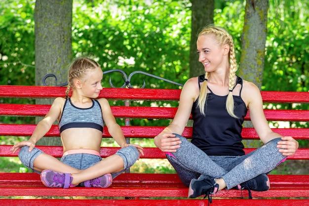 여름 공원에서 벤치에 앉아 운동복을 입고 딸과 어머니
