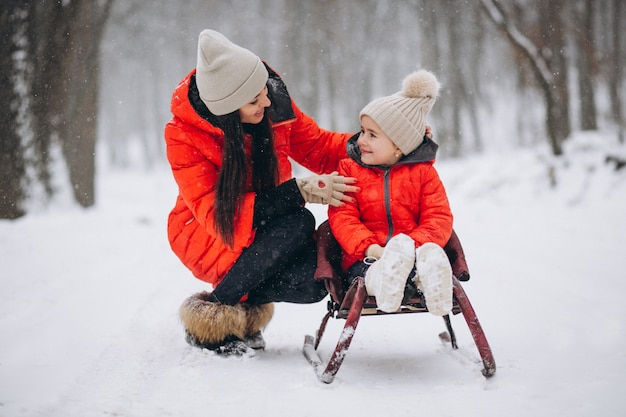 Mother with daughter in winter park sledging