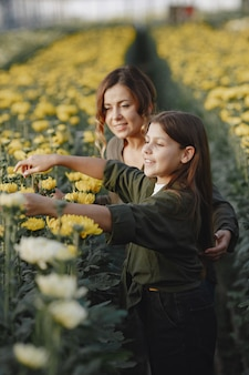Mother with daughter. workers with flowerpoots. girl in a green shirt