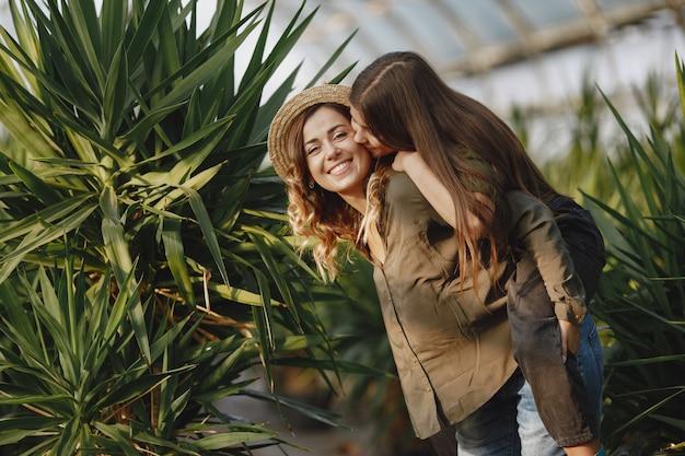 娘と母。フラワープートを持つ労働者。緑のシャツを着た女の子