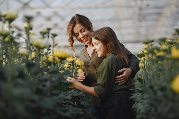 Мать с дочерью. рабочие с цветочными горшками. девушка в зеленой рубашке