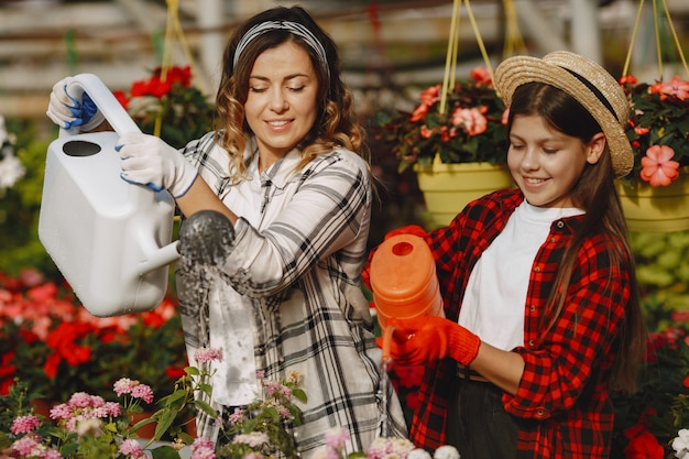Mother with daughter. workers with flowerpoots. people pours flowers