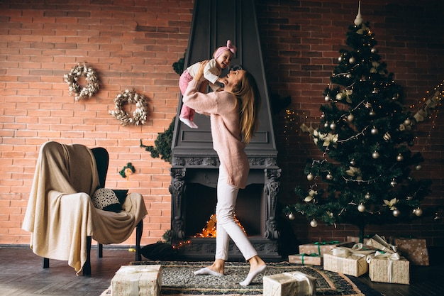 Mother with daughterby the fireplace on christmas