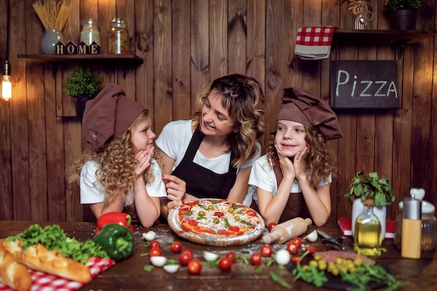 Mother with daughters cooking pizza in kitchen
