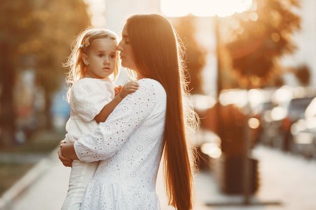 娘が遊んでいるお母さん。白いドレスを着た女性。夕日を背景に家族。