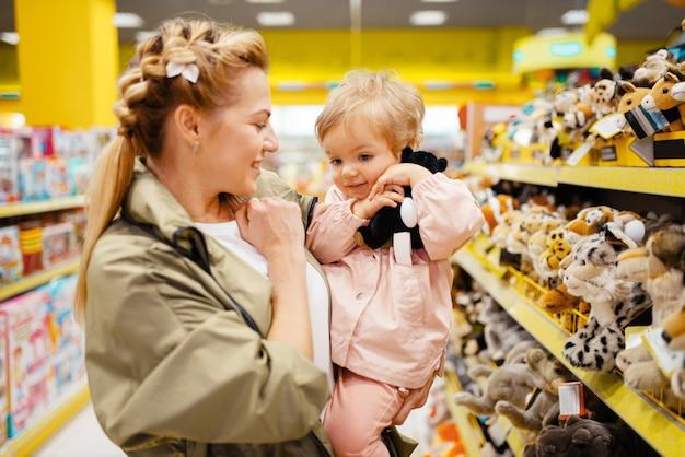 Мать с девочкой, выбирая плюшевую собаку в детском магазине