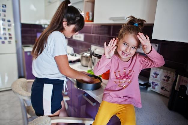 キッチンで料理をしている女の子とお母さん、幸せな子供の瞬間。