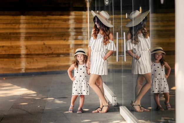 テラスで帽子とドレスの少女と母親