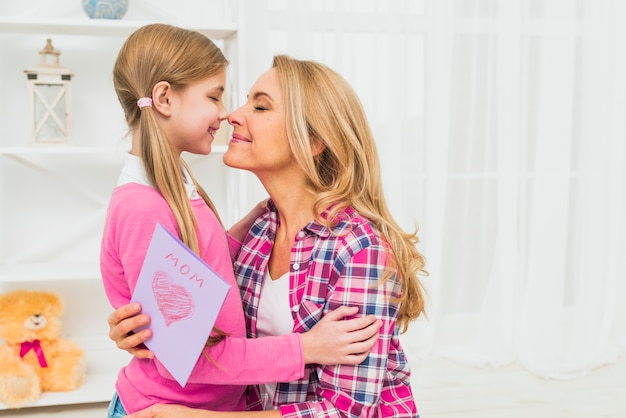 Mother with greeting card touching noses with daughter
