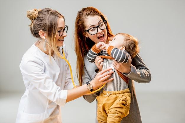 白いオフィスのインテリアに立っている聴診器で聞いている若い女性の小児科医で彼女の男の子と母親