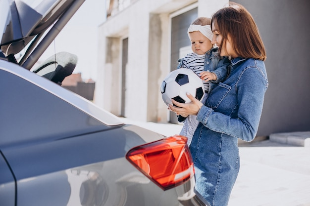 Mother with her baby daughter by the car with football ball