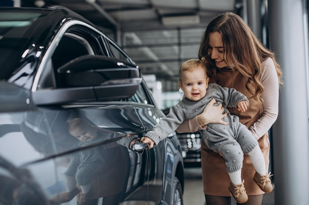 Mother with her baby daughter in a car showroom