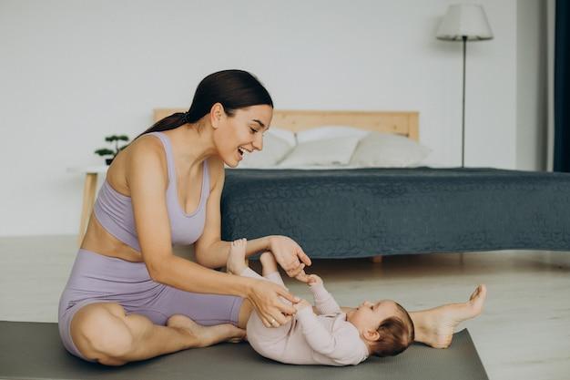 그녀의 아기 딸과 함께 어머니는 집에서 요가 연습