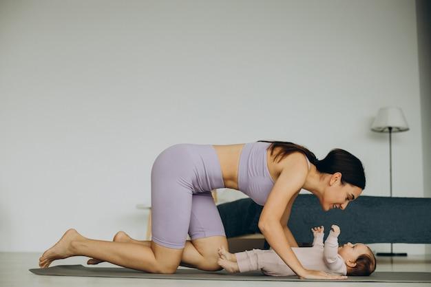 赤ん坊の娘を持つ母親は自宅でヨガを練習します