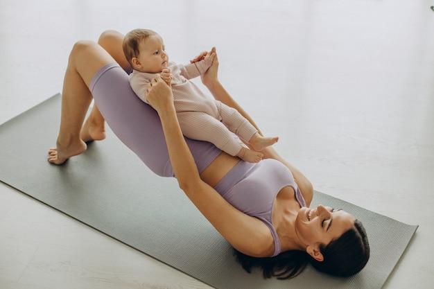 La mamma con la sua bambina pratica lo yoga a casa