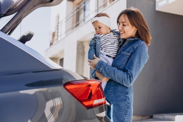 家の近くに駐車した車のそばで楽しんでいる女の赤ちゃんを持つ母親