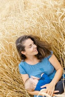 赤ちゃんを持つ母親は、夏に麦畑に座っています。