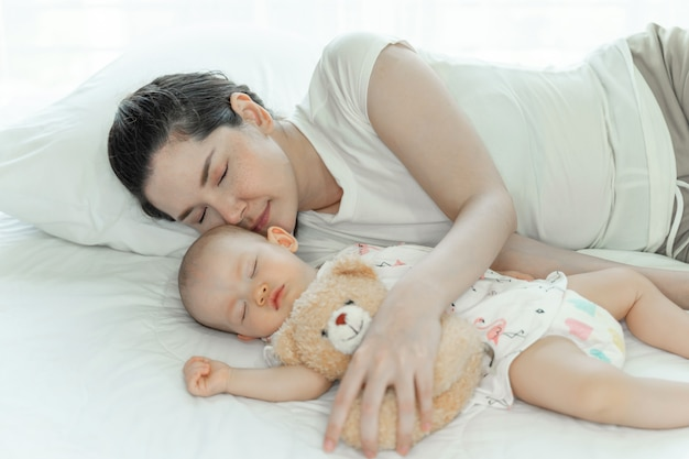 Mother with her baby sleeping on bedroom