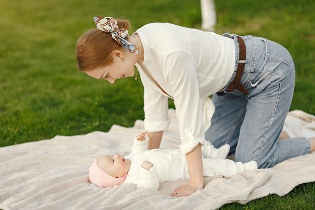 Мама с ребенком проводят время в летнем саду