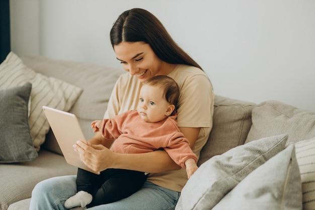 自宅でタブレットを使用して彼女のbbayの女の子と母親