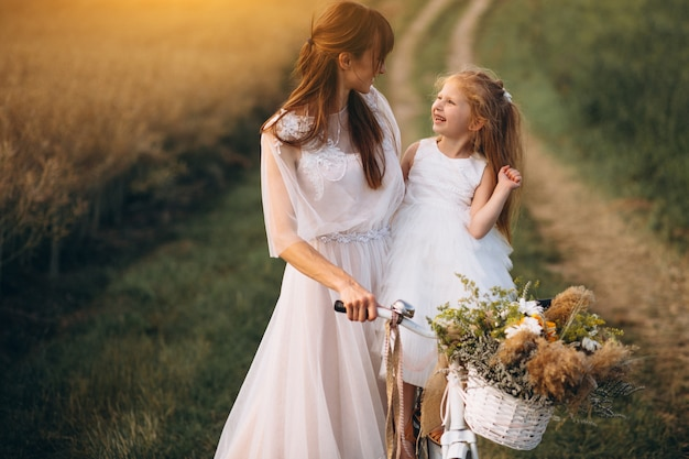 Mother with her child in beautiful dresses with bicycle