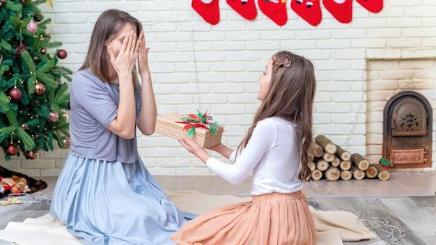 그녀의 딸과 어머니는 집에서 크리스마스 트리 근처 바닥에 선물을주고있다. 행복한 가족 아이디어